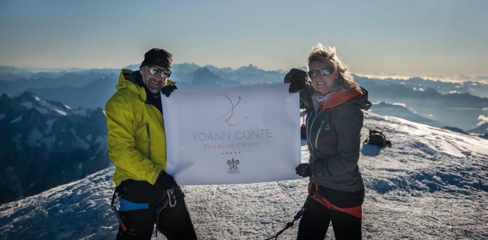 Yoann Conte et son épouse brandissant l'étandard de leur établissement une fois parvenus au sommet du Mont-Blanc, en septembre 2020 DR
